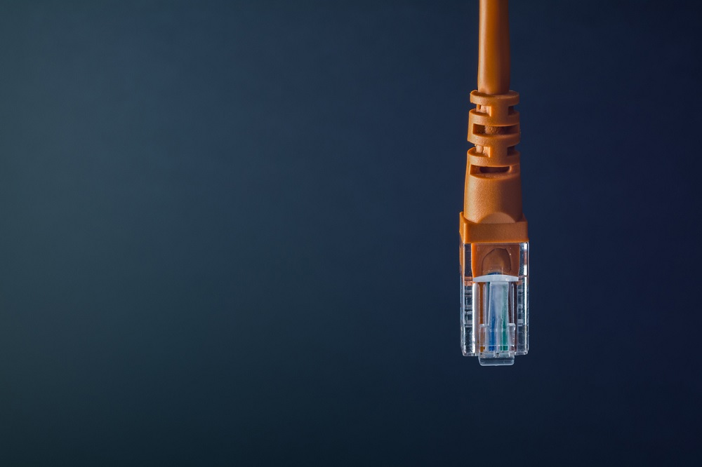 LAN connection orange plastic connector isolated on black background
